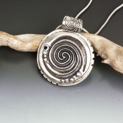 A Silver Double Spiral Pendant with Blue Sapphire